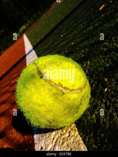 Tennis ball on sideline of court with shadow of net - Stock Image