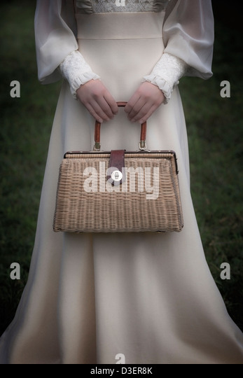 a woman in a victorian dress with a handbag made of bast - Stock Image