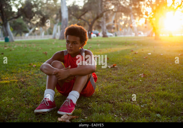 Sad looking boy sitting in park - Stock Image