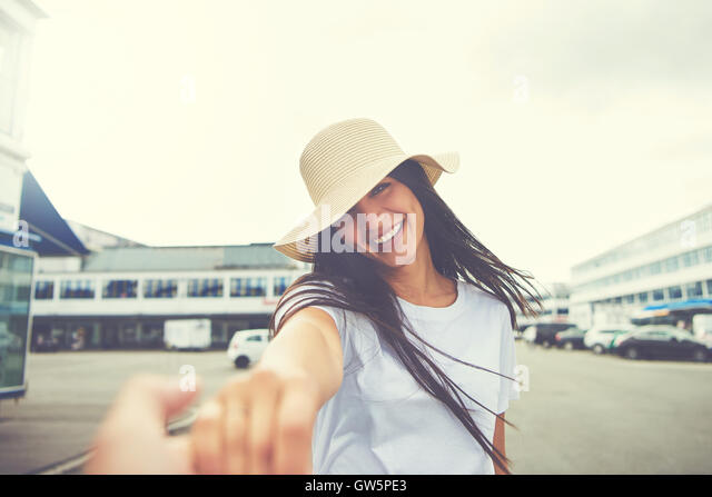 Woman with hat stretches hand toward camera and smiles while standing in parking lot of nearby shopping mall - Stock Image