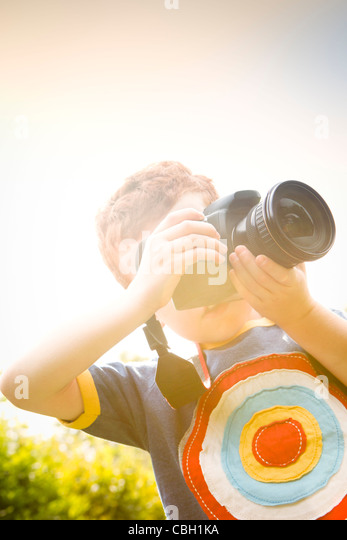 A Young boy, aged 7, using a digital SLR camera in a sunny garden. - Stock Image
