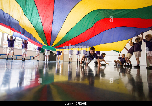 Pupils at a UK primary school playing with a parachute in the school hall - Stock-Bilder