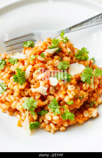 Pearl barley and tomato stew on white platter - Stock Image