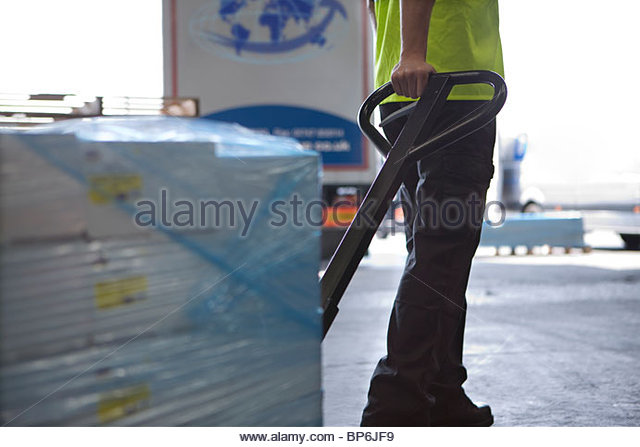 Worker on loading dock pulling inventory on  hand truck - Stock Image