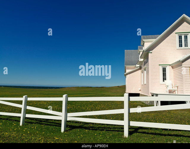 Canada Quebec Gaspesie Riviere la Madeleine pink house and with white fence greenfield against a blue sky - Stock Image