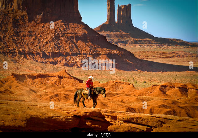 Navajo Indian cowboy riding his horse across colorful red sandstone plateau. Monument Valley Navajo Tribal Park, - Stock Image