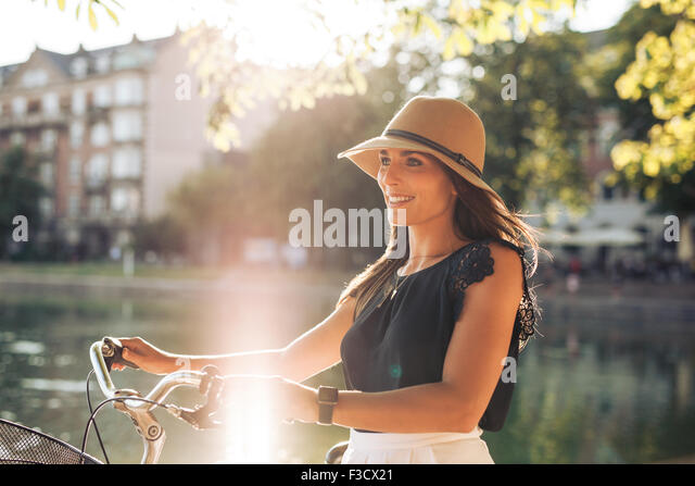 Portrait of happy young woman at the city park walking along a pond with her bicycle. European female model wearing - Stock-Bilder