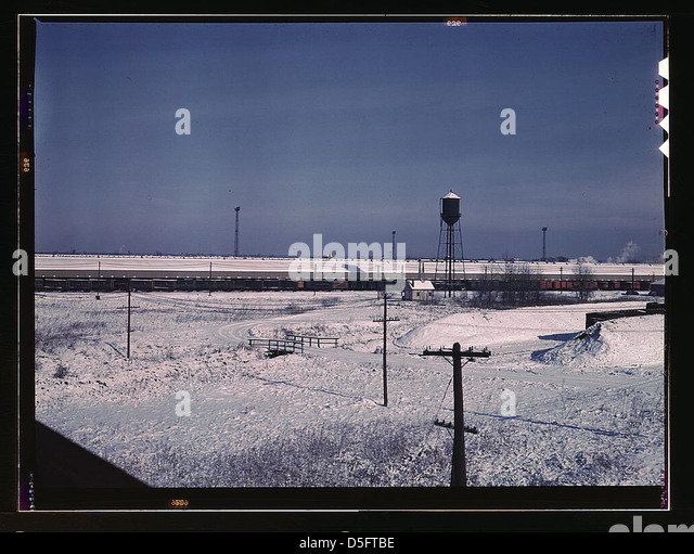 View of a Chicago and Northwestern railroad freight house. A long line of truck trailers are loading and unloading - Stock Image