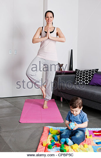 A young mother practicing yoga at home whilst her baby son plays on the floor - Stock-Bilder