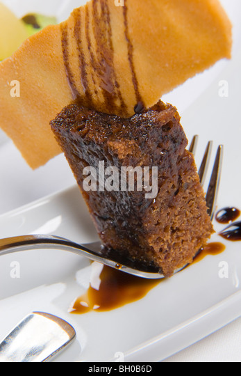 chocolate mud cake on fork served on white plate - Stock Image