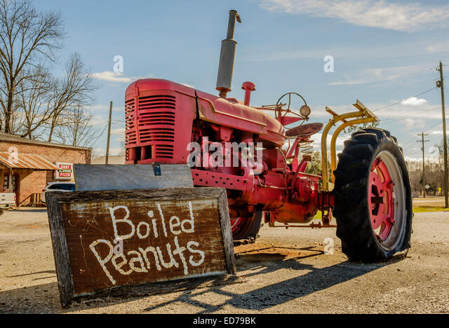 An old red farm tractor holding up a sign selling boiled peanuts in Cecil, Alabama, USA.  Frequently seen in the - Stock Image