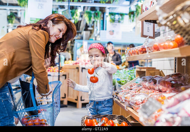 Girl holding tomatoes while standing by mother in supermarket - Stock-Bilder