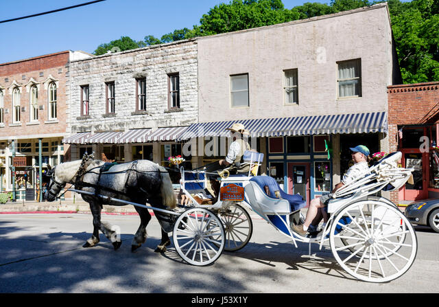 Arkansas Eureka Springs horse drawn carriage driver historic buildings renovated preservation facade stone - Stock Image