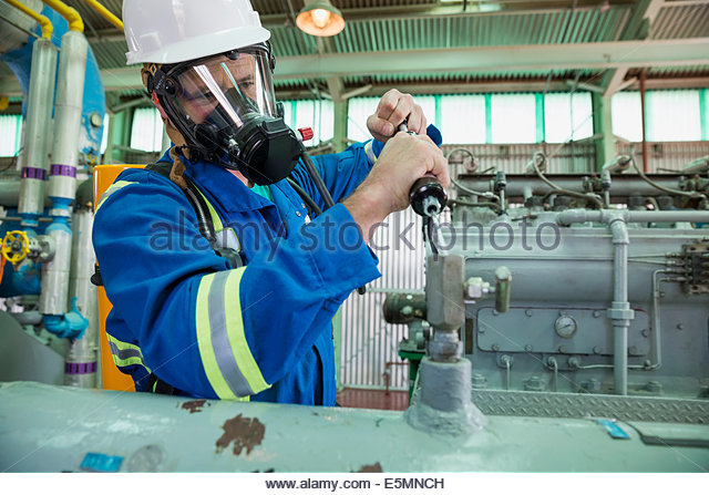 Male worker repairing equipment in gas plant - Stock Image