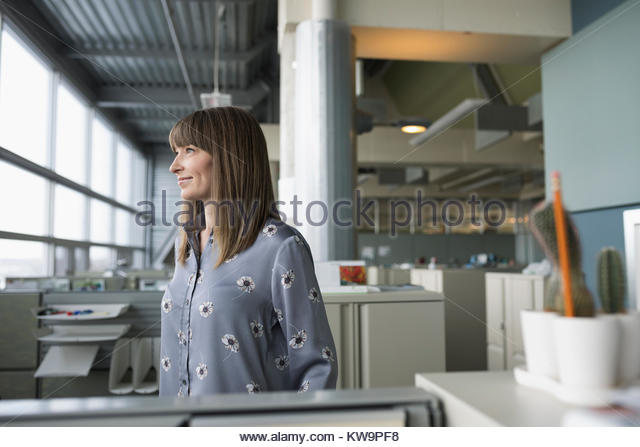Ambitious,confident businesswoman looking away in office cubicle - Stock Image