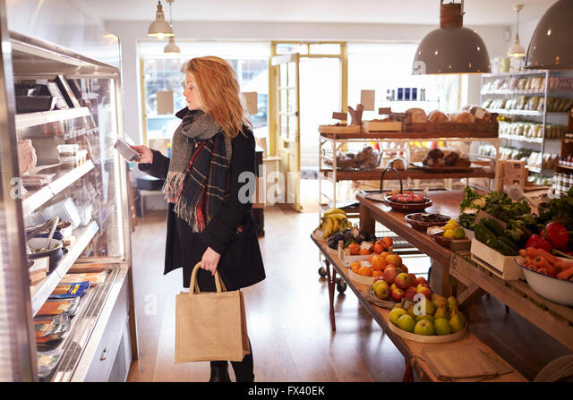 Woman Looking In Refrigerated Display Of Delicatessen - Stock Image