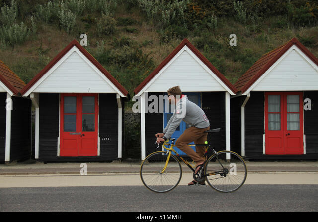 Bournemouth, UK -  11 May: A cyclist rides past an array of beach huts located in Bournemouth beach. General view - Stock Image
