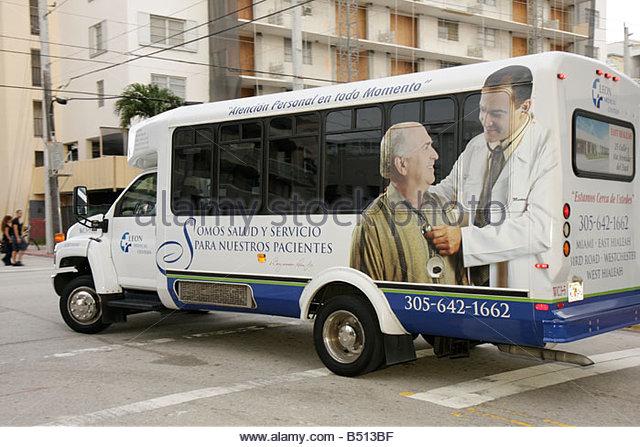 Miami Beach Florida Ocean Drive bus senior transport advertising Spanish language Leon Medical Centers patient service - Stock Image