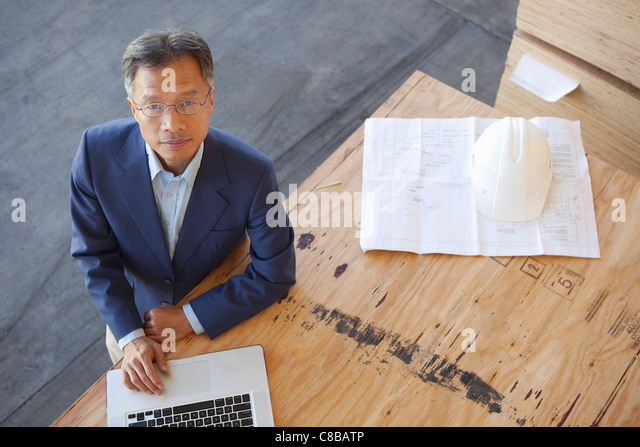 Top view of manager using laptop on plywood in warehouse - Stock Image