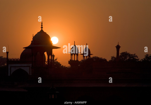 The guard towers of Agra's Red Fort are silhouetted against the setting sun in Agra, Uttar Pradesh, India. - Stock-Bilder