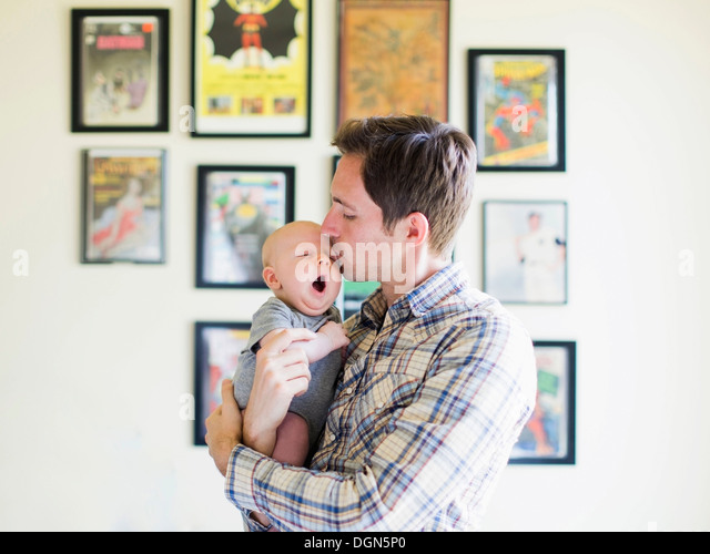 Father kissing baby son (2-5 months) - Stock-Bilder