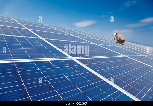 close up solar panel and professional worker installing photovoltaic solar panels - Stock Image