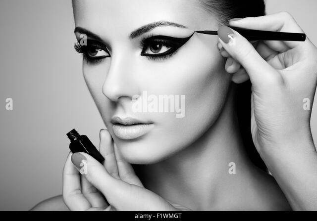 Makeup artist applies eye shadow. Beautiful woman face. Perfect makeup. Black and white photo - Stock Image
