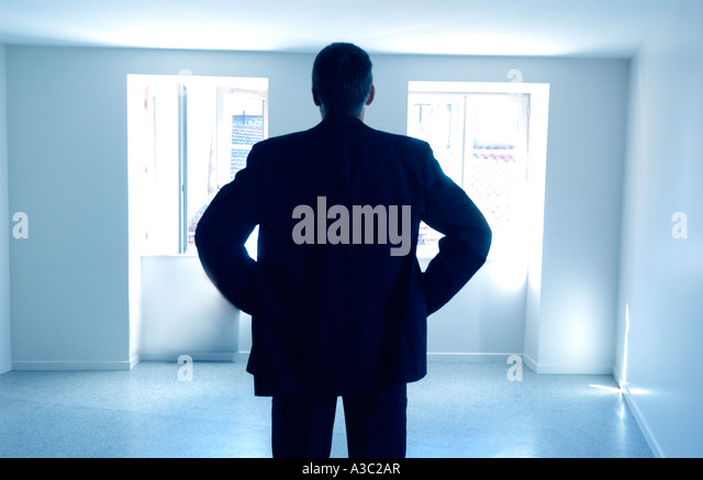 Man standing in an empty room / apartment / house - rear view silhouette - property / owner/ selling / rental / - Stock-Bilder