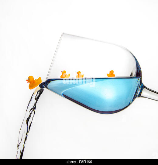 Rubber ducks in a wine glass - Stock Image