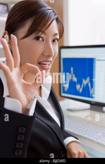 Young businesswoman making OK sign - Stock Image