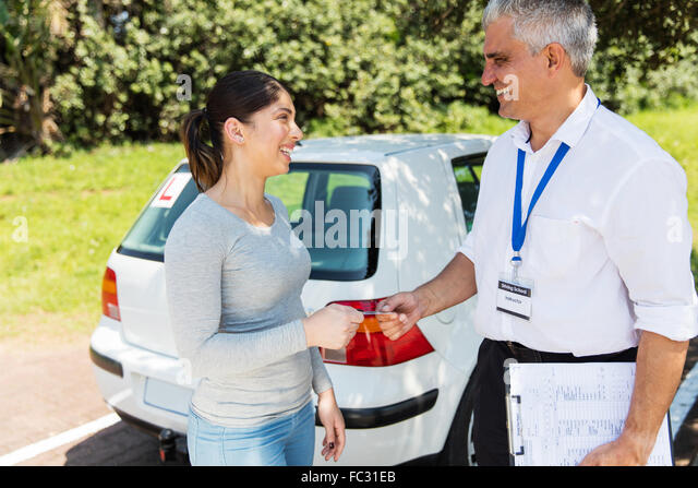 cheerful young woman being handed driver's license by senior driving instructor - Stock Image