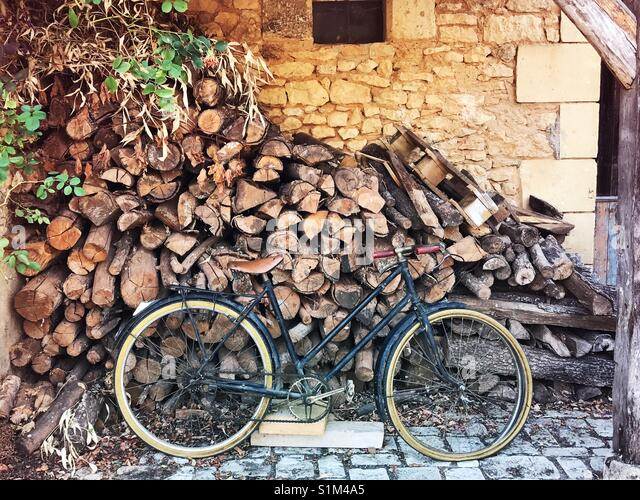 Rustic bicycle leaning against firewood in the market place in Buisson-de-Cadouin, Dordoigne, France. - Stock Image