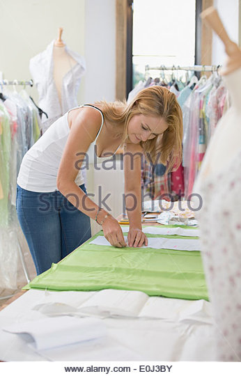 Fashion Designer Sewing Fabric In Studio - Stock Image