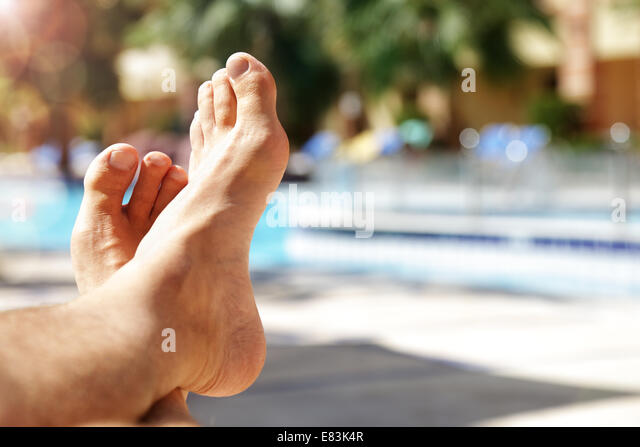 Sunbathing by swimming pool - Stock-Bilder