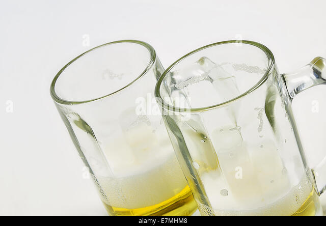 two beer mugs with beer and foam, half full, half empty, on white background, diagonal - Stock Image