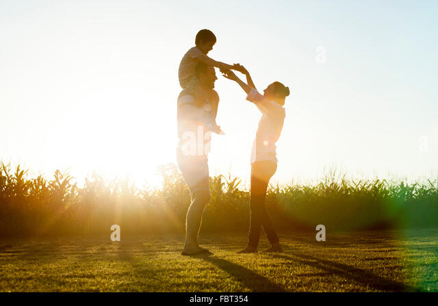 Family with little boy basking in glow of later afternoon sun - Stock Image