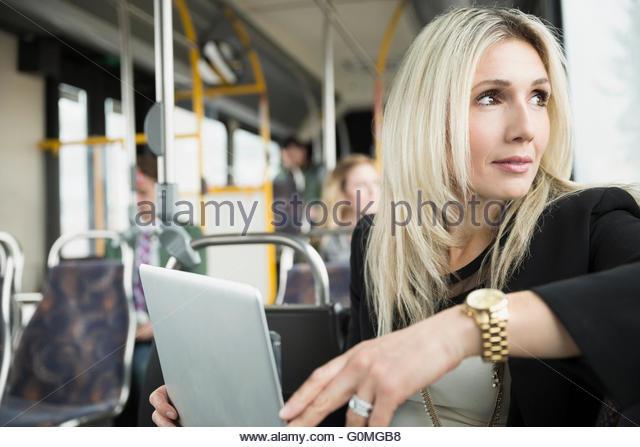 Pensive businesswoman using laptop on bus looking away - Stock-Bilder