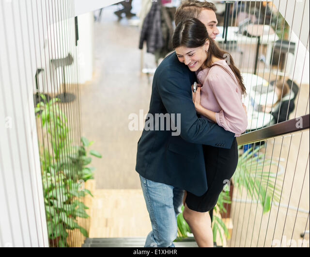 Side view of young business couple hugging on staircase - Stock Image