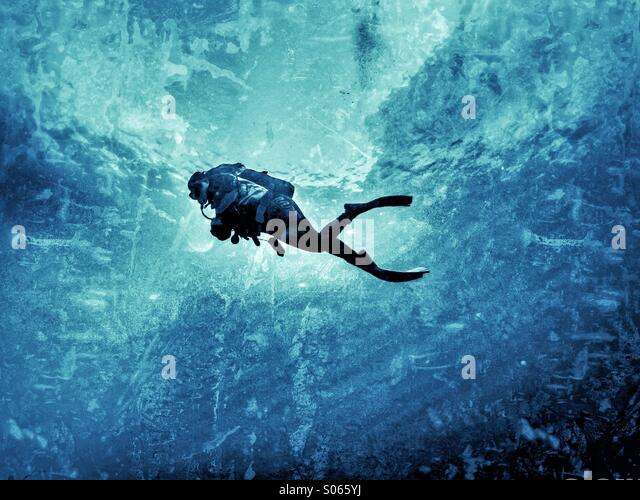 Young female scuba diver swimming in mid water - Stock-Bilder