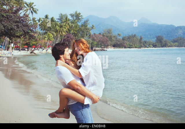 happy young family on the beach, couple during honeymoon - Stock Image