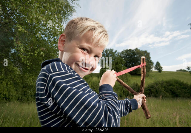Cheeky young boy slingshot blond smiling - Stock Image