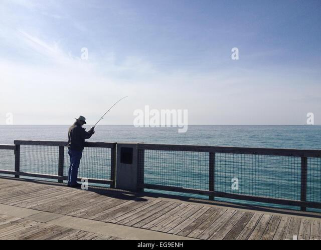Man in pier fishing - Stock Image