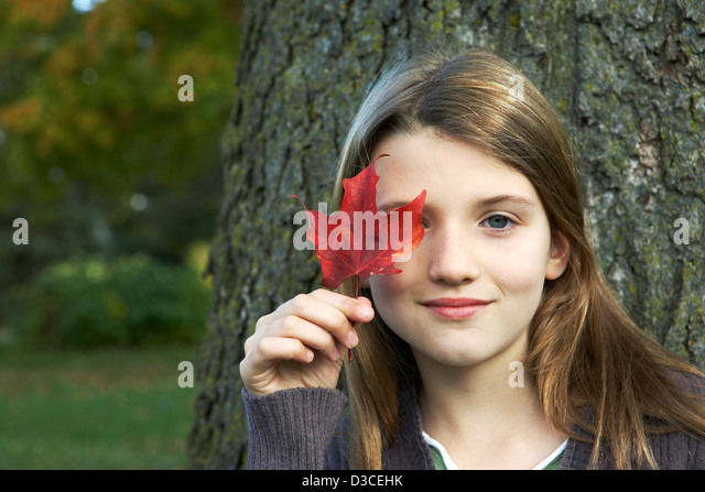Beautiful child holding red leaf - Stock Image