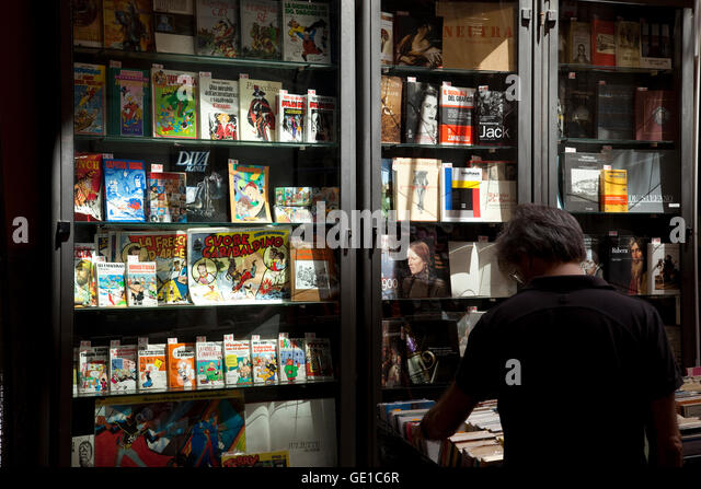 A man browses through books at a book stall in Naples, Italy. - Stock Image