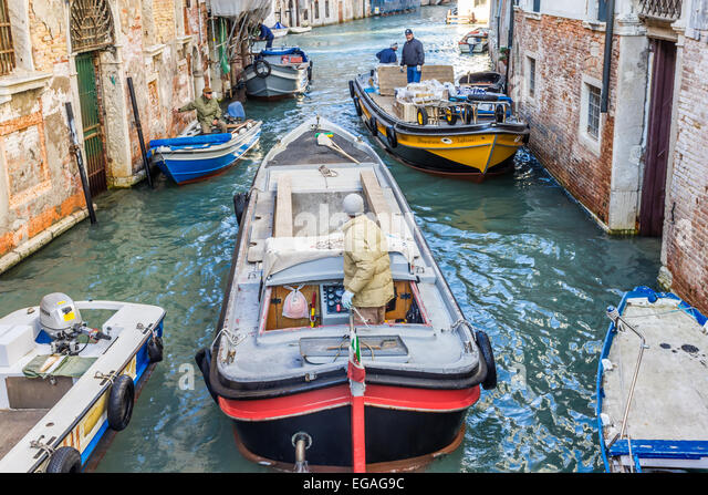 Two workboats on congested canal in Venice - Stock Image