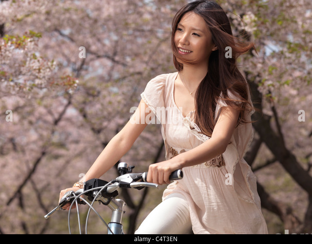 Young smiling Asian woman riding a bicycle in a park past blooming cherry trees - Stock-Bilder
