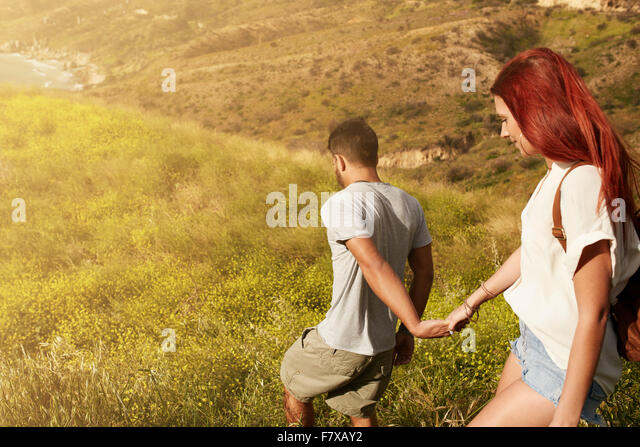Outdoor shot of young couple enjoying on their vacation, walking down a peak holding hands. Caucasian couple hiking - Stock-Bilder