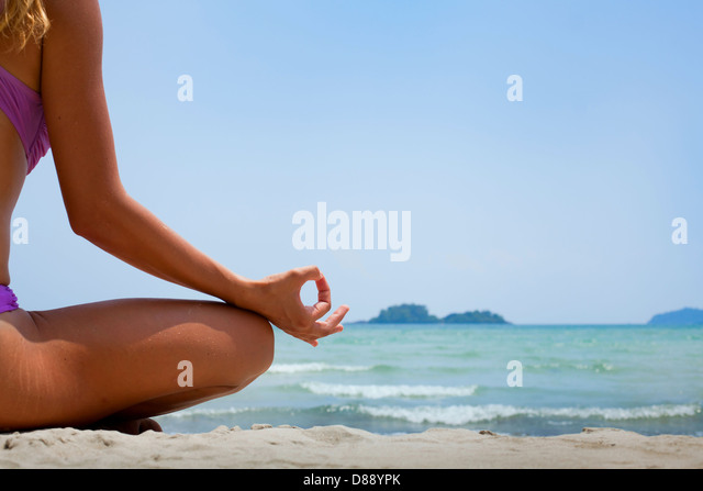 yoga background, woman in lotus position meditating on the beach - Stock Image