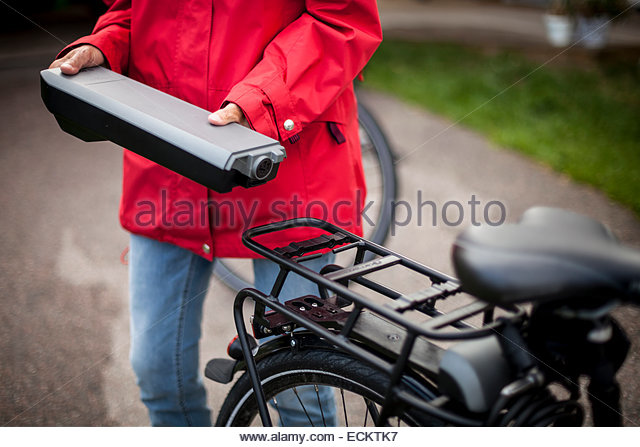 Midsection of senior woman holding battery by electric bicycle on street - Stock Image