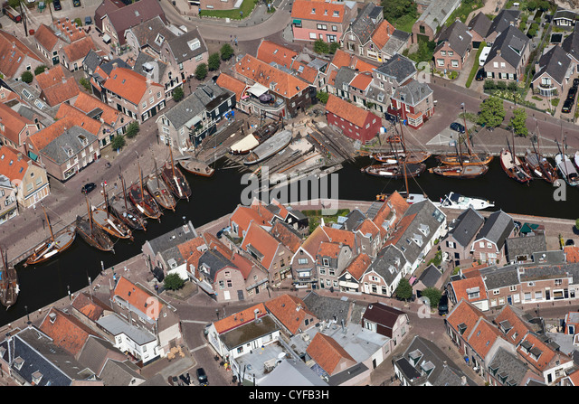 View on center of village and harbour. Shipyard for repair and construction of old fashioned fishing boats. Aerial. - Stock Image